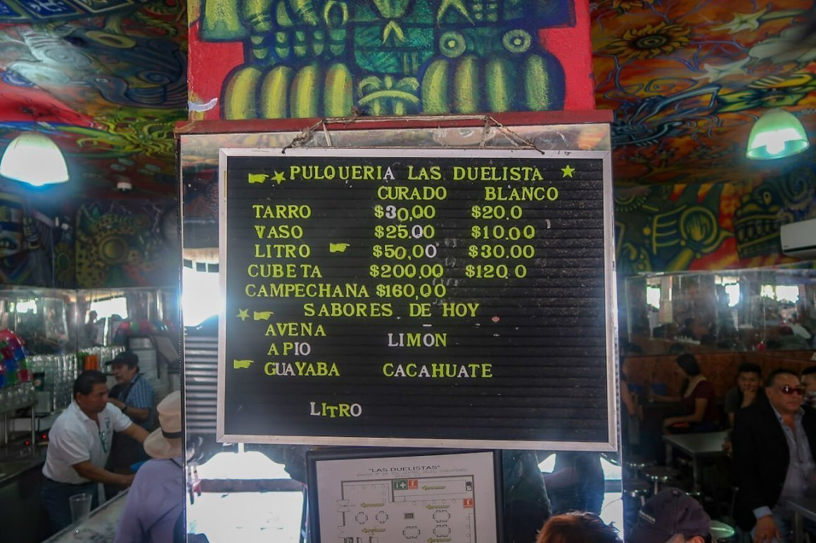 Pulque menu at Las Duelistas with patrons and servers in background