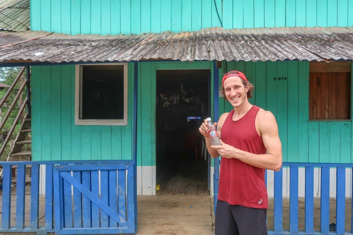 Chris holding a bottle of viche, a home-brewed alcoholic Colombian drink