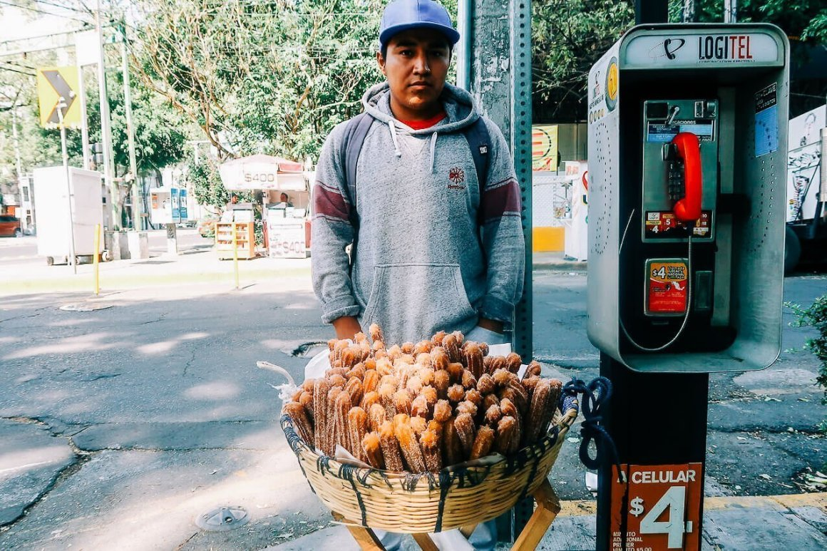 young man selling churros on the street in mexico city