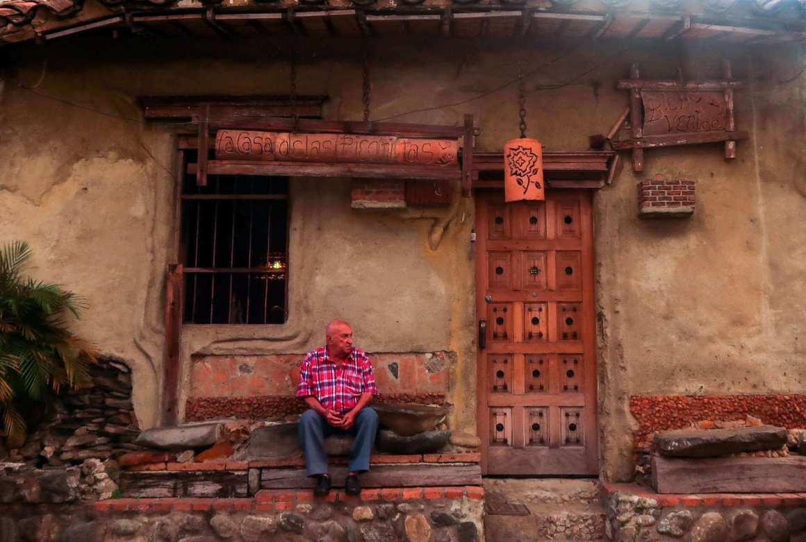 Envigado best things to do guide cover image of a man sitting in front of a house