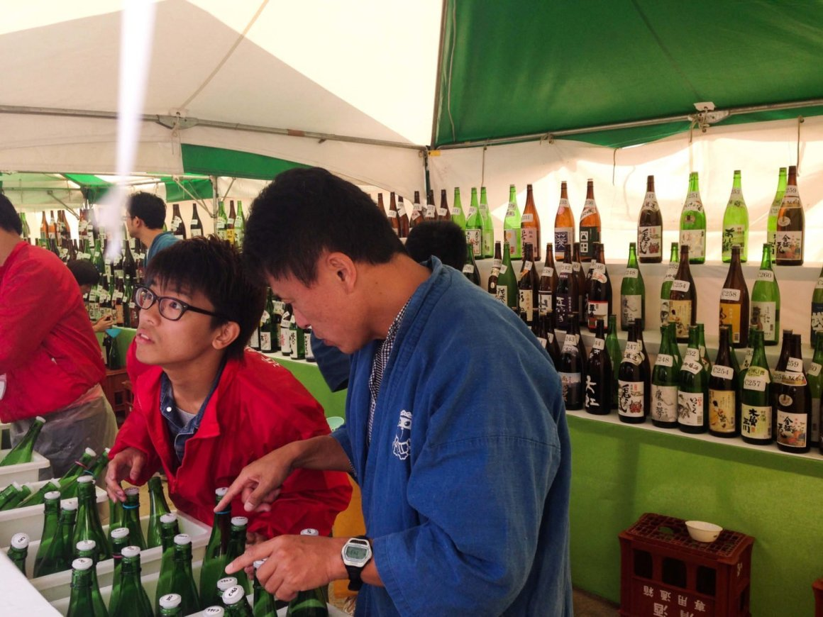 sake brewers pouring tasters at the Saijo Sake Festival