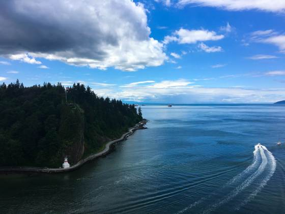 Vancouver travel blog cover of Stanley Park and a boat going through Georgia Straight