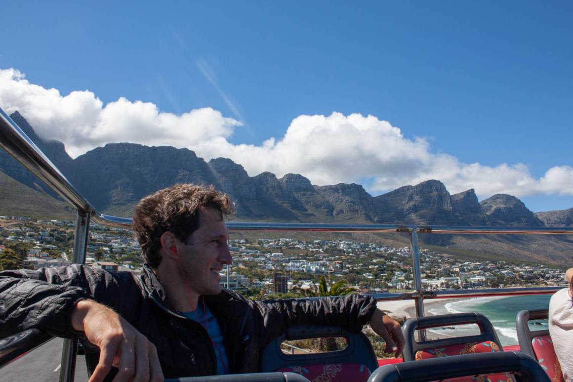 Chris chilling on the back of the hop-on hop-off bus with the Twelve Apostles in the background