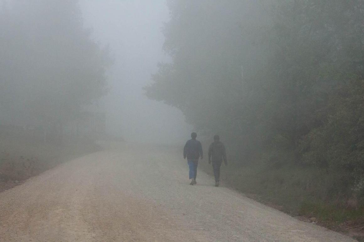 Guys walking along misty road