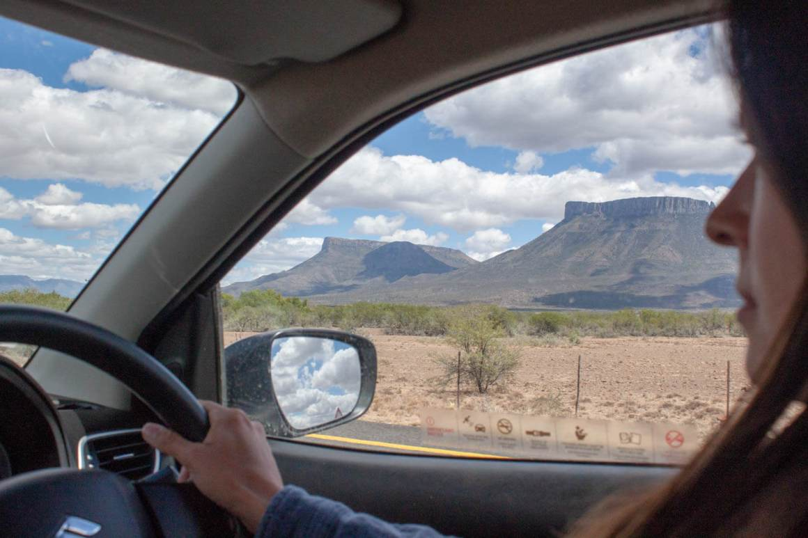 View through driver's side window of mountains, desert, and clouds in rear view mirror