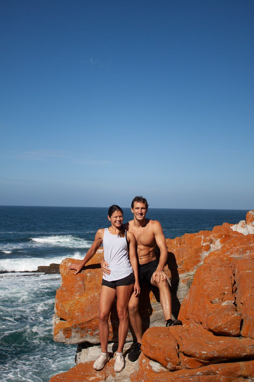 Kim and Chris with red rock backdrop along a coastal hike in Stormsriver.