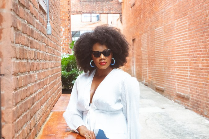 Black woman in white blouse and blue skirt wearing sunglasses.