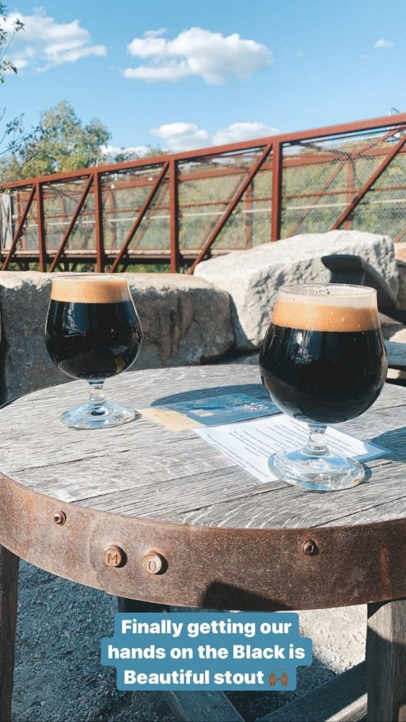 Dark beer in a glass on a table with a bridge in the background