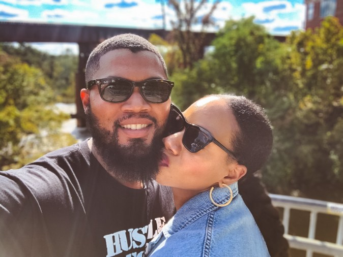 Black woman with a ponytail kissing a black man with a beard