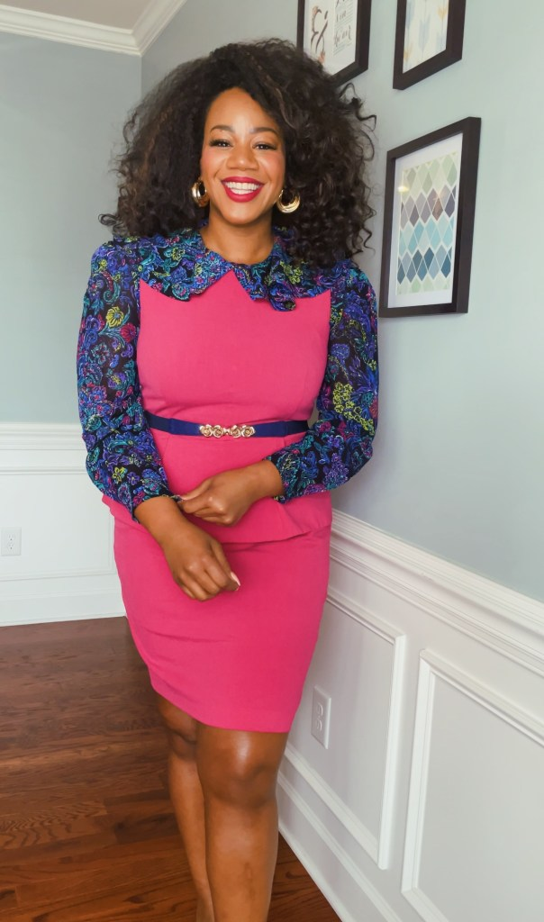 Smiling black woman with natural curly hair wearing a hot pink dress over a blue paisley shirt