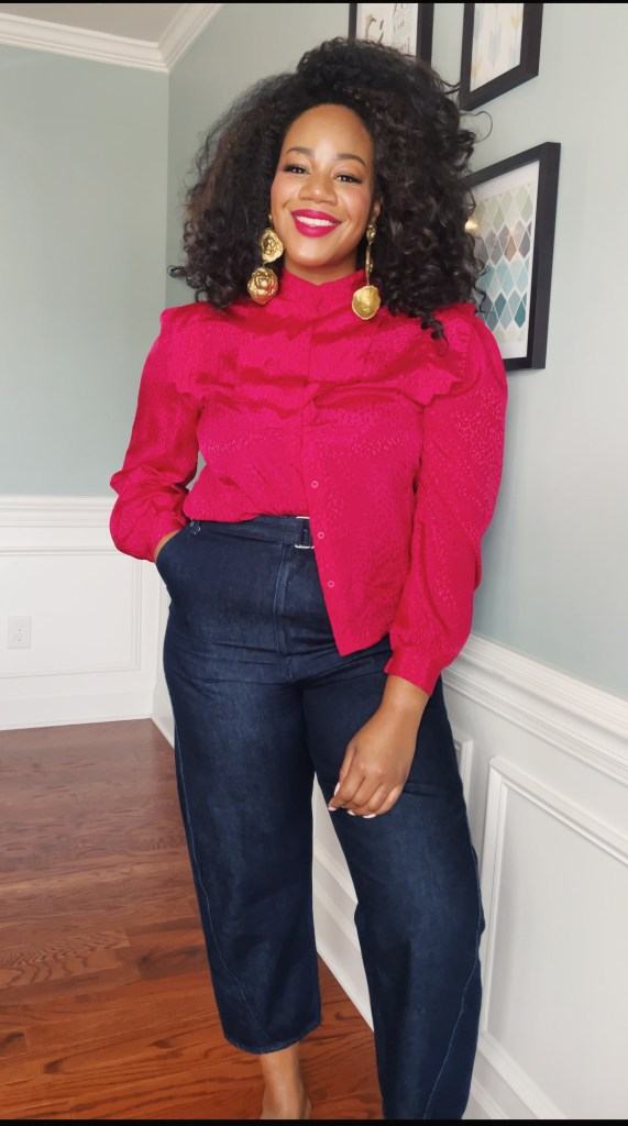 Smiling black woman with natural curly hair wearing a hot pink blouse and blue jeans