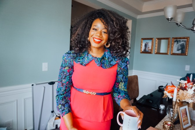 Smiling black woman wearing a hot pink dress over a blue paisley shirt in a dining room