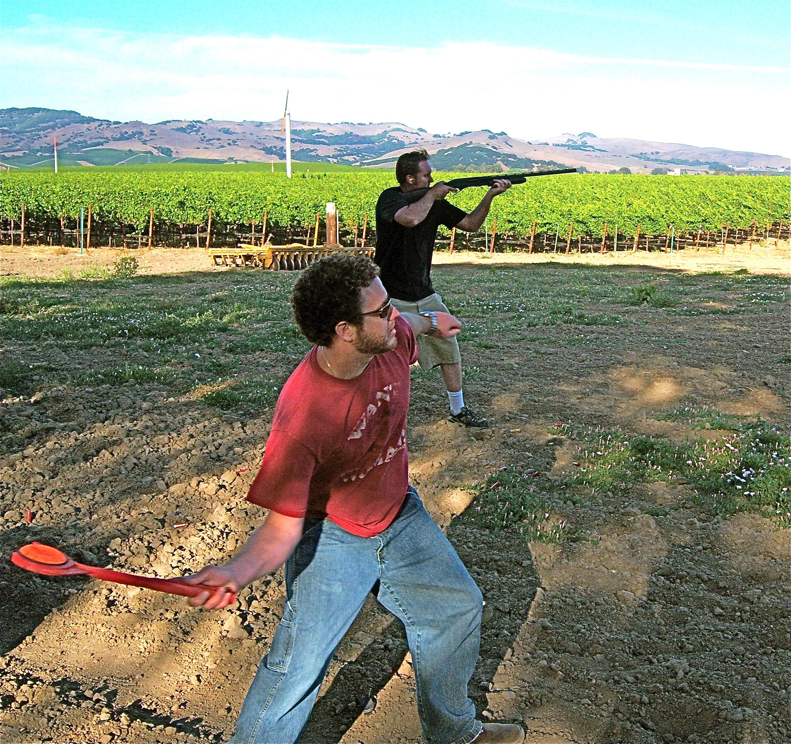 """John, """"Stringbean"""" takes aim with his Remmington 870, while Bennie, """"Flapjack"""" mans the thrower.     John, """"Stringbean"""" takes aim with his Remmington 870, while Bennie, """"Flapjack"""" mans the thrower."""