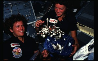 Photographic documentation showing 41G crew activities. Astronauts Mission Specialist 1 (MS1) Kathryn D. Sullivan (left), and MS2 Sally K. Ride show off what appears to be a bag of worms, a product of their creativity. The bag is a sleep restraint and the majority of the worms are springs and clips used with the sleep restraint in its normal application. Clamps, a bungee cord and Velcro strips. 255-STS-41G-07-021