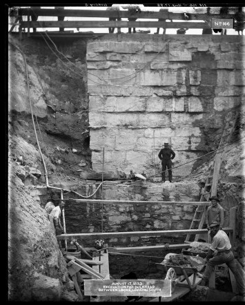 """Image shows men working down in an excavation site, their equipment precariously supported by two by four planks of wood. One man observes the workers from a shelf halfway down the excavation, while the legs of people standing some twenty feet above at the top of the image. Label on the original photograph reads, """"August 17, 1893. Excavation for bulkhead between locks, looking south."""""""