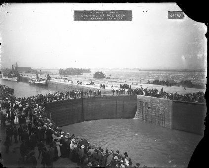 """Image shows crowds of people standing on each side of the new lock, as well as on the lock gates which are closed. Label on original photograph reads, """"August 3, 1896. Opening of Poe Lock. At intermediate gate."""""""