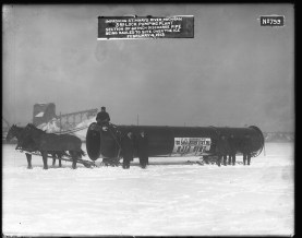 """Image shows two horses pulling a 60 inch pipe across snow. The man holding the reins sits atop the pipe itself, while five other men (two of them in long winter coats, the other three dressed warmly and probably workers) stand next to the pipe facing the camera. A label on the pipe, upside down, reads: This pipe manufactured by the East Jersey Pipe Co. Paterson N.J. [New Jersey]."""""""