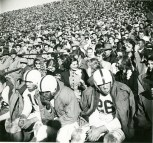 Original Caption: MSC Story. View of football crowd and players on bench during game. Local ID: 306-PS-514-S-50-12347
