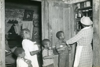 """Negro woman tenant storing her canned food in a pantry built on back porch, with the help of her grandchildren. Allendale County, South Carolina. September 1940."" (Image ID: 16-G-162-S-7146)"