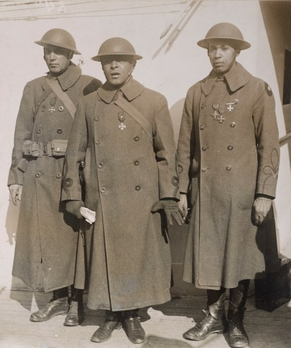 Major J.R. White, Lieutenant Colonel Otis B. Duncan (the highest ranking black officer in WWI), and Lieutenant W.J. Warfield of the 369th (NY) and 370th (IL) return home in February 1919. All three officers received decorations from both the French and the United States. Note the men of the 93rd now wore the British trench helmet worn by the rest of the AEF. Local Identifier, 165-WW-127-9.