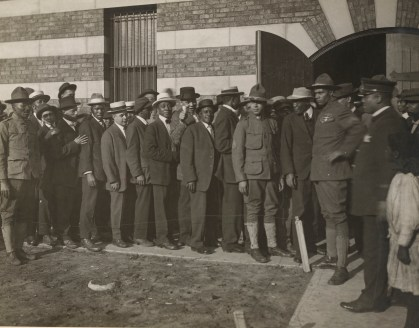 Black men line up to enlist for active service in the 8th Illinois Infantry Regiment (colored), Chicago, IL 1917. The 8th Illinois became part of the 93rd Provisional Division, and the Army re-designated it as the 370th Infantry Regiment. Local Identifier, 165-WW-127-122.