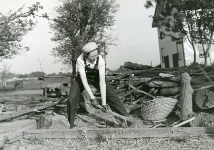 """Miss Mildred Saums of Three Bridges, Hunterdon County, NJ, can do as good a job at the family wood pile on her widowed mother's farm as her brother who runs the farm. She helps with the morning and evening chores. Daytimes she works as chief clerk at the Flemington Auction Market cooperative Association."" Date Taken: May 1942 (Local ID: 16-G-168-N-3983)"