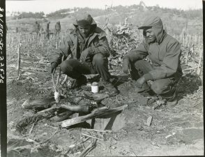 "(Local Identifier: 111-SC-354712) Johnnie Washington (NYC, NY) and Wilbert H. Davis, both of the 25th Infantry Regiment, decide to do a little ""Home Cooking"" at Pong Dong, Korea and barbecue a pig to supplement their regular rations."