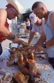 "(Local Identifier: 330-CFD-DF-ST-96-00276) ""CM3 Dan Ward, left, CM2 Russell Couhran, right, both mechanics; and, equipment operator EO1 Steven Moose Musnicky, Seabees from Port Hueneme, Calif, take charge of the pig roast. The pigs were cooked the night before and now the men are busily carving the carcass for the Independence Day cookout at Camp Pleso."""