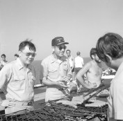 "(Local Identifier: 330-CFD-DN-SN-85-11086) ""Rear Admiral (RADM) Lawrence Chambers, commander, Carrier Group Three (center), and his chief of staff, Captain (CAPT) Ming Chang participate in the cookout during Stand Down Day aboard the aircraft carrier USS CORAL SEA (CV 43)."""
