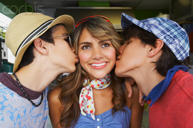 Close-up of a teenage girl being kissed by her two boyfriends