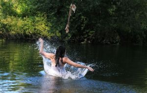 Immy splashing into a lake after swinging over the water on a rope