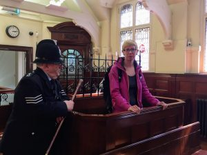 Sarah in the court docks with a policeman keeping her in check