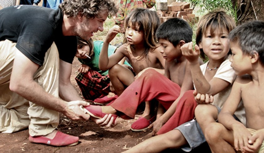 Blake Mycoskie, the founder of TOMS, puts a pair of red shoes on a child's feet.