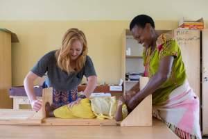 A Peace Corps Volunteer helps measure a baby in Rwanda.