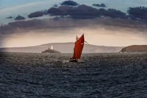 a lugger with a red sail