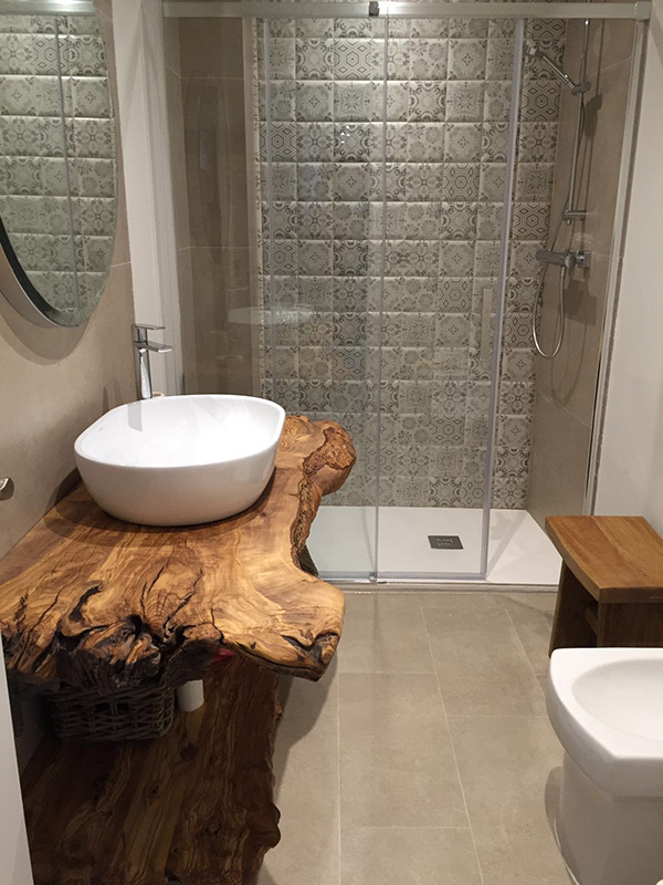 A small bathroom with a rough wood countertop