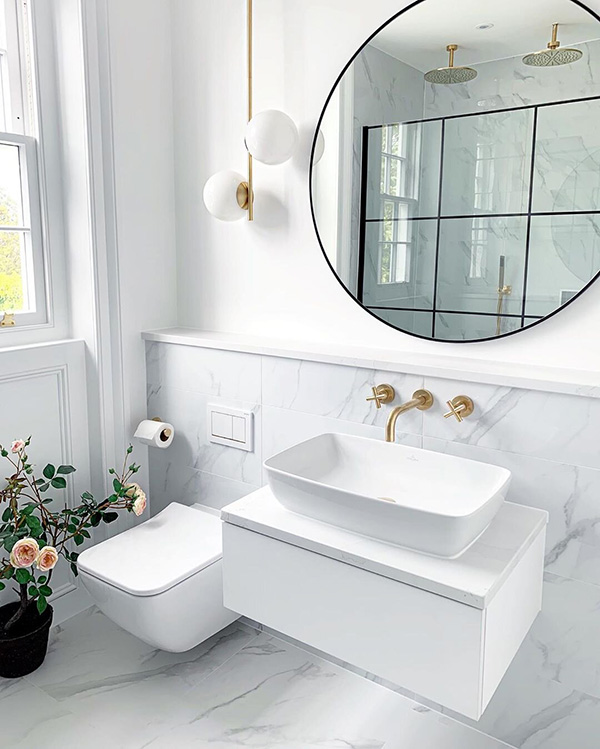 A small, modern bathroom with marble and golden accents
