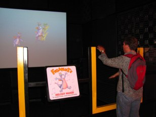 """""""Kurt plays Figment's Melody Maker at ImageWorks"""" by Castles, Capes & Clones is licensed under CC BY-ND"""