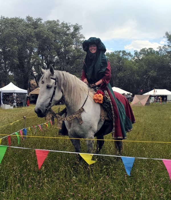A white person in fancy medieval garbin deep red & green sits, smiling, atop a beautiful grey horse.
