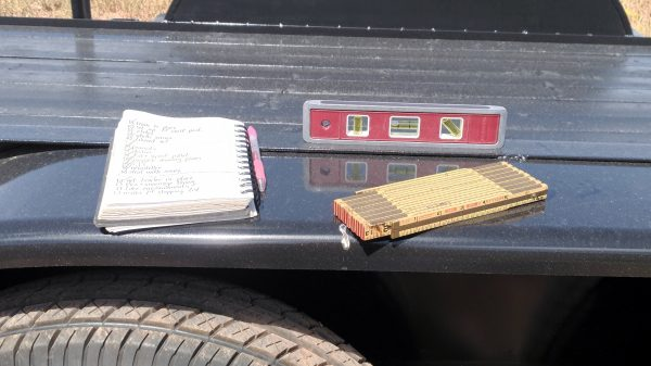 On the thing that goes over the tires on the trailer, there's a notepad with pink pen, a short carpenter's level, & an old-fashioned folding carpenter's ruler.