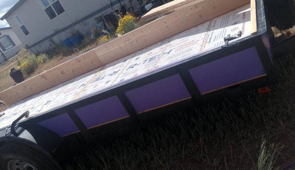 The trailer, seen from the side. The boards of the box are visible between the upright shafts of the railing. The purple looks pretty cool against the black railing.