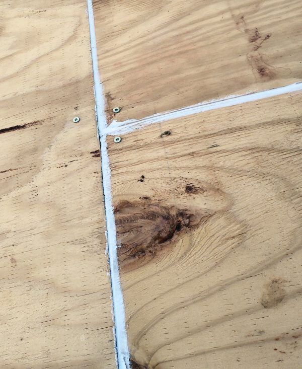 Three pieces of plywood meet at the corners. They're held down with wood screws, & the gaps in between are filled with white caulk.