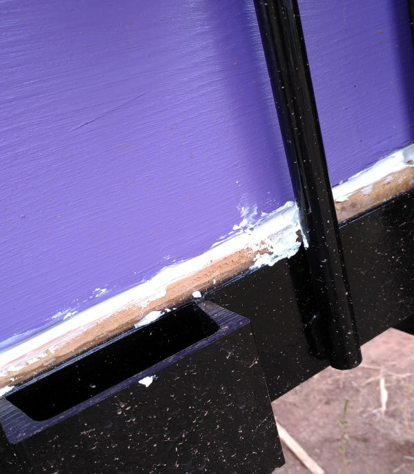 There's a big purple-painted board above, a thin unpainted board below, & a really messy line of caulk in between.
