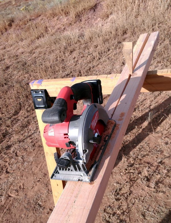 A 2x4 board, partway through being cut in half the long way. A circular saw sits in the middle of the board, & nehind it a wedge of wood holds the two already-cut parts separate.