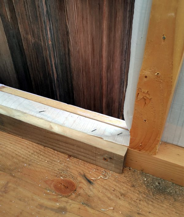 The bottom part of the door hole, which now has a piece of wood fastened along the bottom.