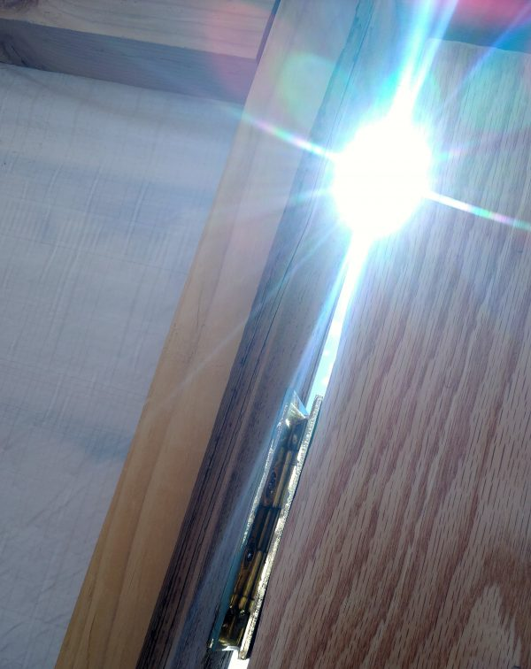 The door from the inside again, close up on the gap where the hinges are. The sun is shining brightly through the gap in a way that recalls a Michael Bay lens flare. DRAMATIC