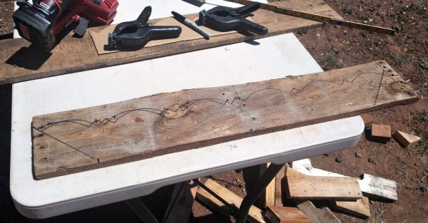 A rough, weathered board lays on a table outside. The same trim pattern that runs up the corners of the tinker's wagon is traced on it in sharpie.