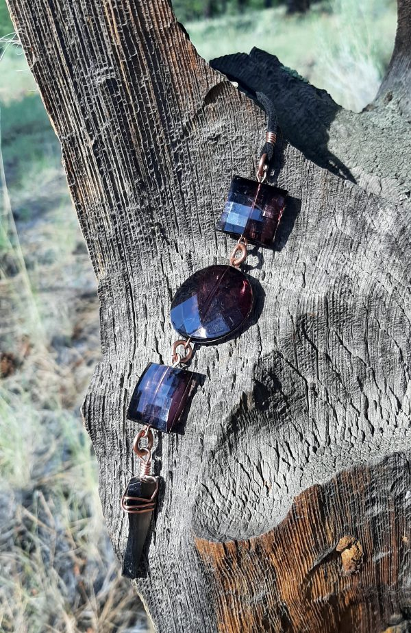A pendulum, deep purple beads connected with copper, is draped over part of the stump; the scoop shape cradles the pendulum in a really photogenic way.