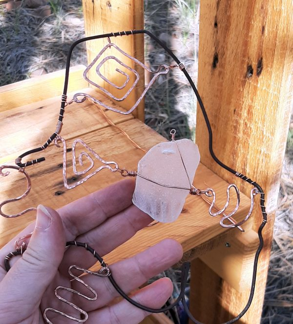 Yes, my finger is holding the seaglass piece in place, but also I've made another loop at the top of it with thinner wire, which will hold it right once I've attached that to something else.