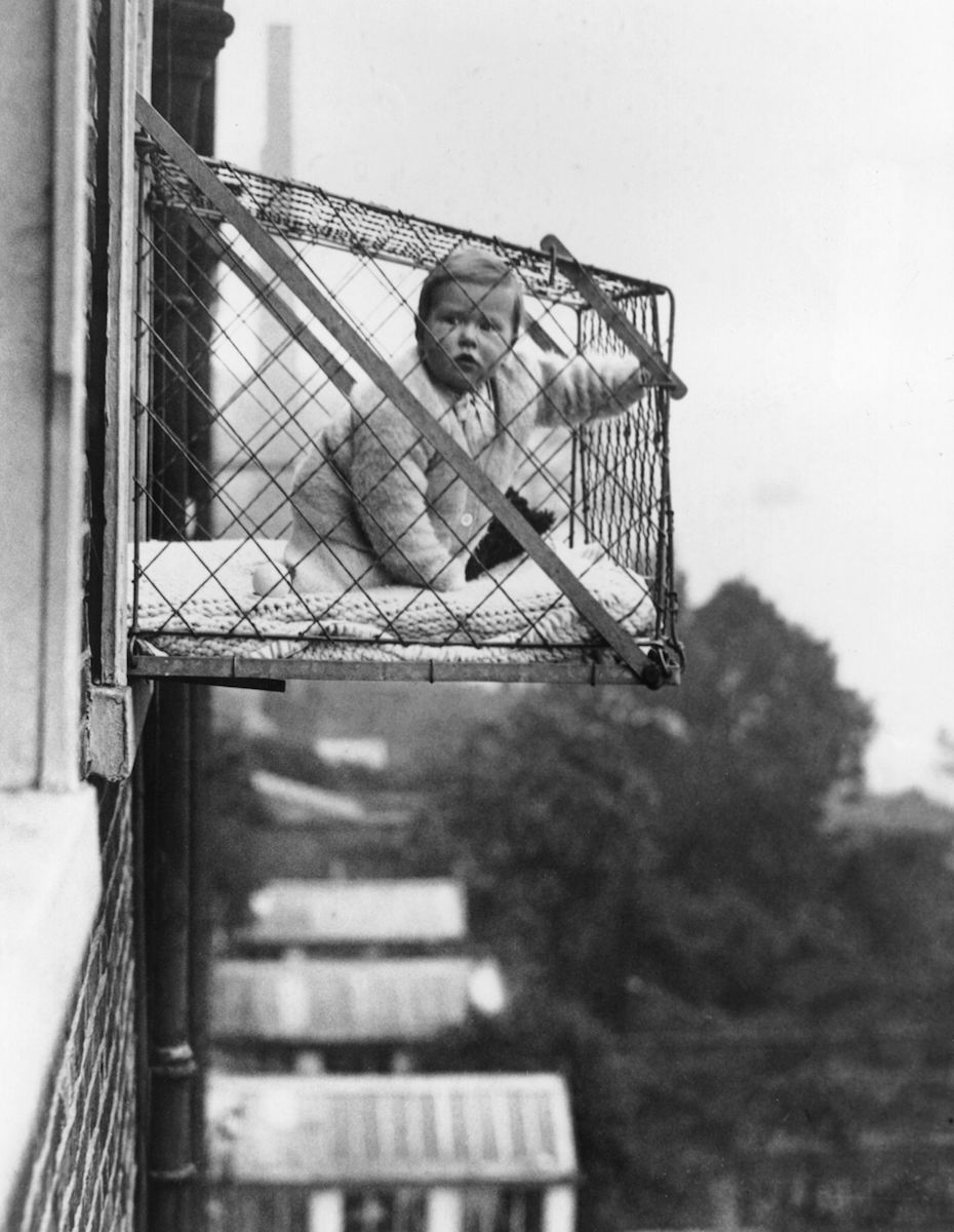 Hanging infant-sized cage out of a London apartment window